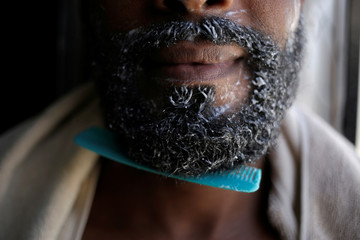 A Cuban migrant, who seeks asylum in U.S. poses for a picture as he washes his beard at El Buen Pastor migrant shelter in Ciudad Juarez