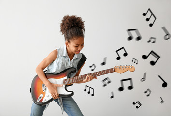 African-American girl playing guitar against light background