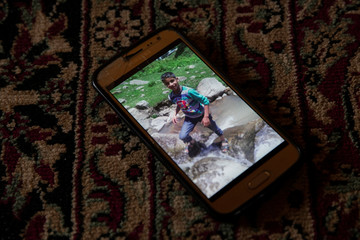 A photograph of Atif Mir, 12, who was taken hostage by militants and later killed in crossfire with Indian troops, is seen on his father's phone, in Bandipore