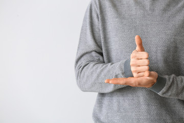 Young deaf mute man using sign language on light background