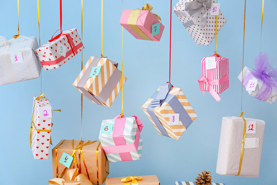 Creative Christmas calendar with gift boxes on color background