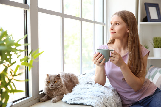 Beautiful woman with cute cat near window at home