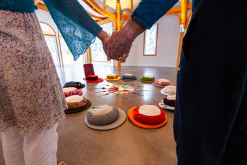 Worshipers hold hands in prayer room. A close up view on the held hands of two spiritual people. Standing together around the Native American twelve color wheel. Believed to bring health and wisdom.