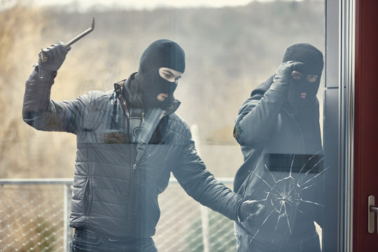 Einbrecher mit Brecheisen schlagen Glas ein