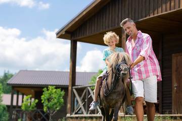 Father feeling memorable while son riding little brown horse