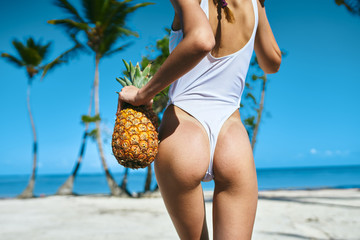 woman with pineapple on the beach Wall mural