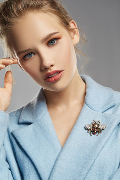 Portrait of lady, wearing sky blue coat with brooch in view of bee with contrasting stripes and wings covered with pearls. The woman with black flicks is looking at camera, posing on gray background.