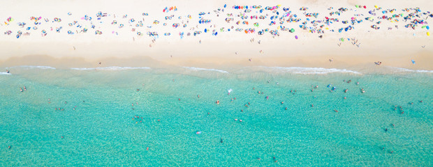 Aerial view crowded public beach with colourful umbrellas, Aerial view of sandy beach with tourists...