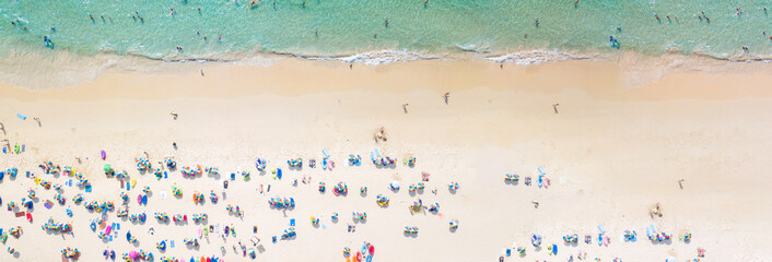 Aerial view crowded public beach with colourful umbrellas, Aerial view of sandy beach with tourists swimming in beautiful clear sea water.