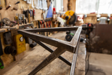 Geometric metal frame inside a workshop. A closeup view on the triangular top of a geometric metal frame created inside a blacksmith's workshop. Finished product of a metalworker.