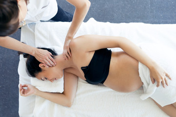 Pregnant woman receiving osteopathic or chiropractic treatment in neck in a clinic.