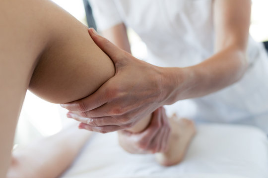 Masseur massaging the pregnant woman's legs in spa center.