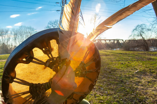 Shaman holds sacred objects outdoors. A close up and backlit view of a Native American drum and two eagle feathers in the hand of a man during sunset. Sacred objects symbolize wisdom and virtue.
