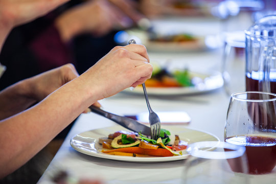 Food served at a conference lunch break. A close up and side view of a woman's hands using a knife and fork to eat a freshly prepared avocado salad during a conference lunch in formal setting.