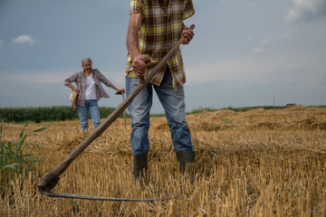 Unrecognizable farmer working in the field with his wife