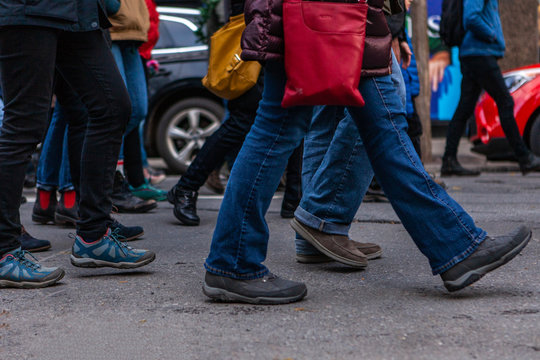 Environmental activists march in city. Many legs are viewed marching in a town center as environmentalists demonstrate together, bustling street scene during a community protest.