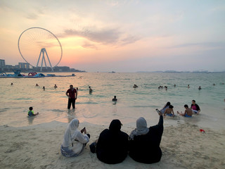 People take selfie as they enjoy the sunset on the beach at Jumeirah Beach Residence in Dubai