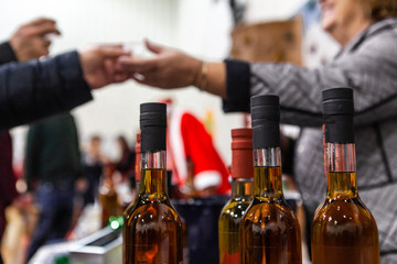 Seasonal products sold at Xmas market. Bottles of homebrewed mulled wine are seen close-up at a Christmas exposition, a shopper is seen exchanging money with a seller, blurry in the background.