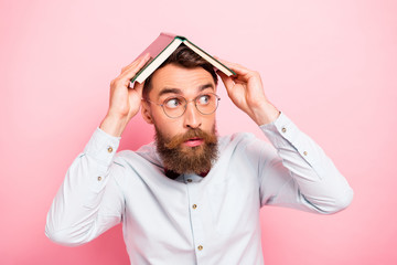 Close-up photo of scared anxious nervous guy holding opened book on head isolated pastel background