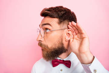 Close-up photo of funny funky smart concentrated hipster gentleman holding palm near ear catching familiar sound isolated pastel background