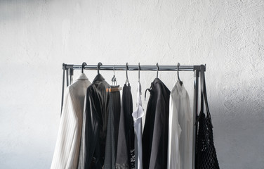 stylish clothes hanging on hangers on white background