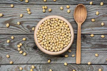 Flat lay photo dried raw soya in wooden bowl and spoon on wooden background. Soybeans in a bowl with ladle. Natural decoration with soy.