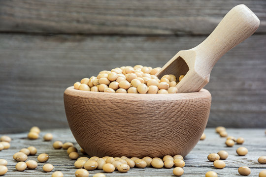 Dried raw soya in wooden bowl and measuring cup on wooden background. Soybeans in a bowl with ladle. Natural decoration with soy.