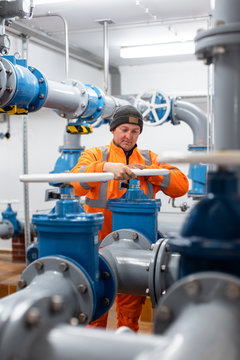 Diligent worker in public water utility turning a valve to open a pipe
