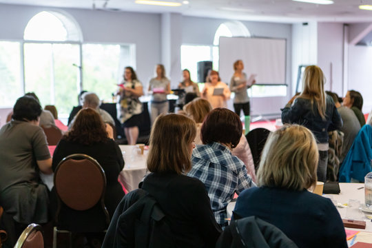 Atmosphere during corporate conference. A rear view of an audience watch a group of professional women stand on stage and give a presentation. People watch on and learn from colleagues.