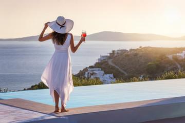 Attraktive Frau in weißem Sommerkleid genießt den Sonnenuntergang am Pool mit einem Aperitif in...