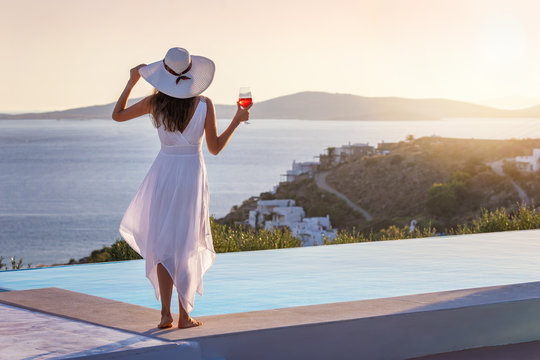 Attraktive Frau in weißem Sommerkleid genießt den Sonnenuntergang am Pool mit einem Aperitif in der Hand