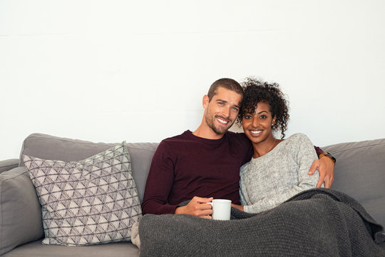 Multiethnic couple sitting on couch hugging