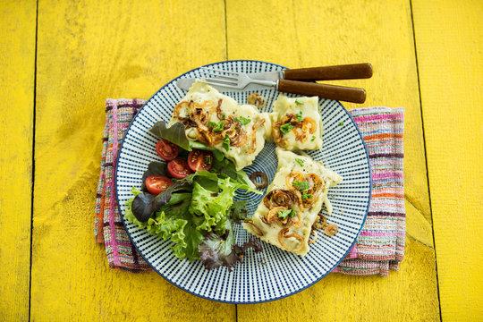 Maultaschen mit gerösteten Zwiebeln, Käse, Salat und Tomaten, Studio