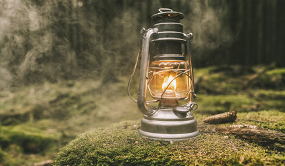Hiker ignite a Gasoline lantern in the forest. authentic close-up shot. Travel concept image