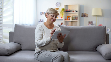 Happy aged woman watching photos on tablet and smiling, spending free time