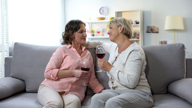 Happy mother-in-law and daughter drinking wine and communicating at home