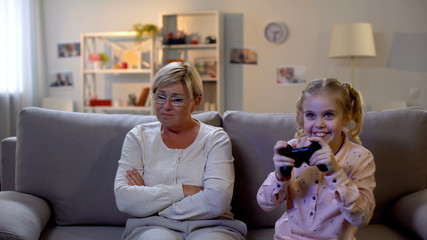 Cheerful schoolgirl playing video game with joystick alone, ignoring granny