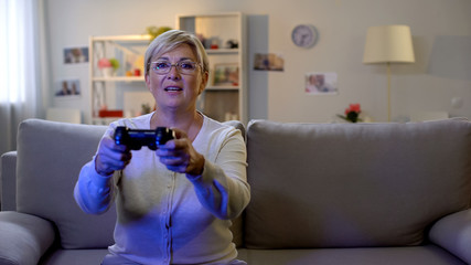 Happy mature lady playing video game on console, sitting home on sofa, leisure
