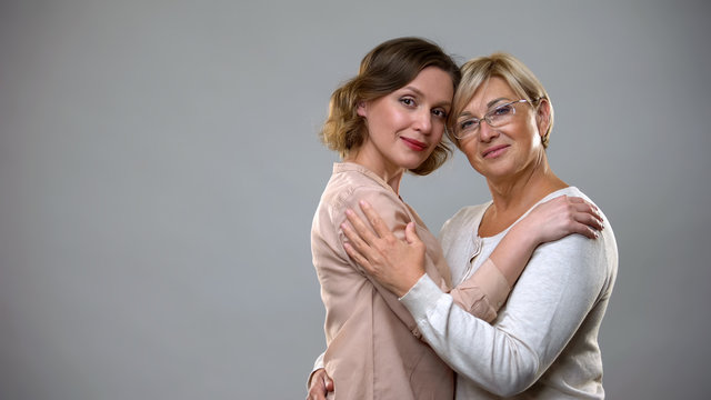 Adult daughter and mother hugging looking in camera, tender family relations
