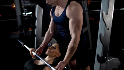 Woman doing barbell bench press in gym, exercise under trainer supervision