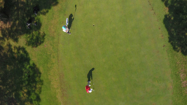 Aerial view of golf players and their shadows in Lloret, Catalonia, Spain.