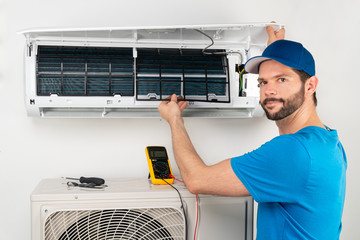 Installation service fix  repair maintenance of an air conditioner indoor unit, by cryogenist technican worker checking the air filter in blue shirt baseball cap