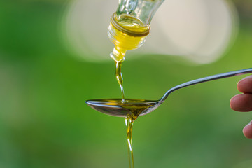 Pouring Olive oil into spoon on Green park garden background