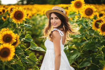 Photo sur Plexiglas Tournesol Portrait of a smiling woman in a straw hat. field with blooming sunflower at background