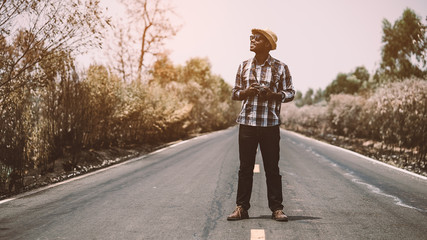 African man photographer traveling in countryside road.