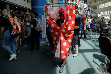 An attendee poses for a picture as they arrive in a costume to enjoy Comic Con International in San Diego