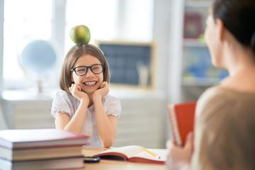 Girl with teacher in classroom.