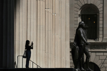 A tourist uses her phone to take a photo on Wall St., during a period of high temperatures, in New York City