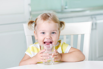 Happy smiling kid with glass of water,child have a drink. Wall mural