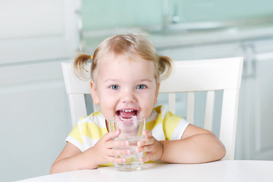 Happy smiling kid with glass of water,child have a drink.